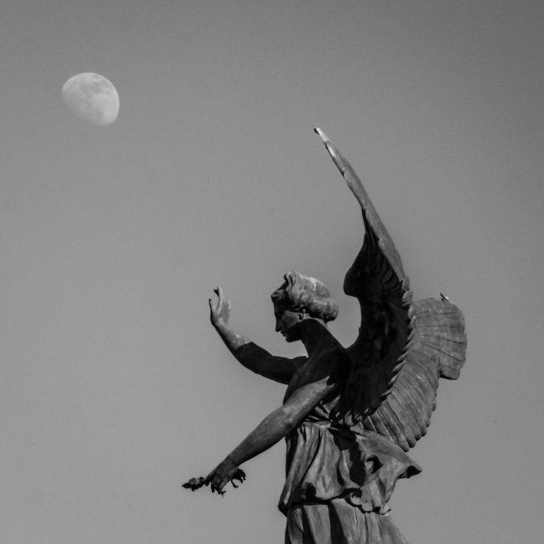 Angel of the George-Étienne Cartier monument directing the moon
